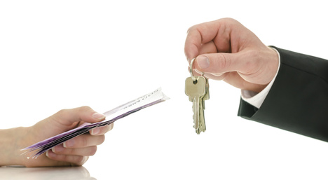 Closeup of male hand giving house keys to a woman in exchange for money. Concept of final step in purchasing a new house.